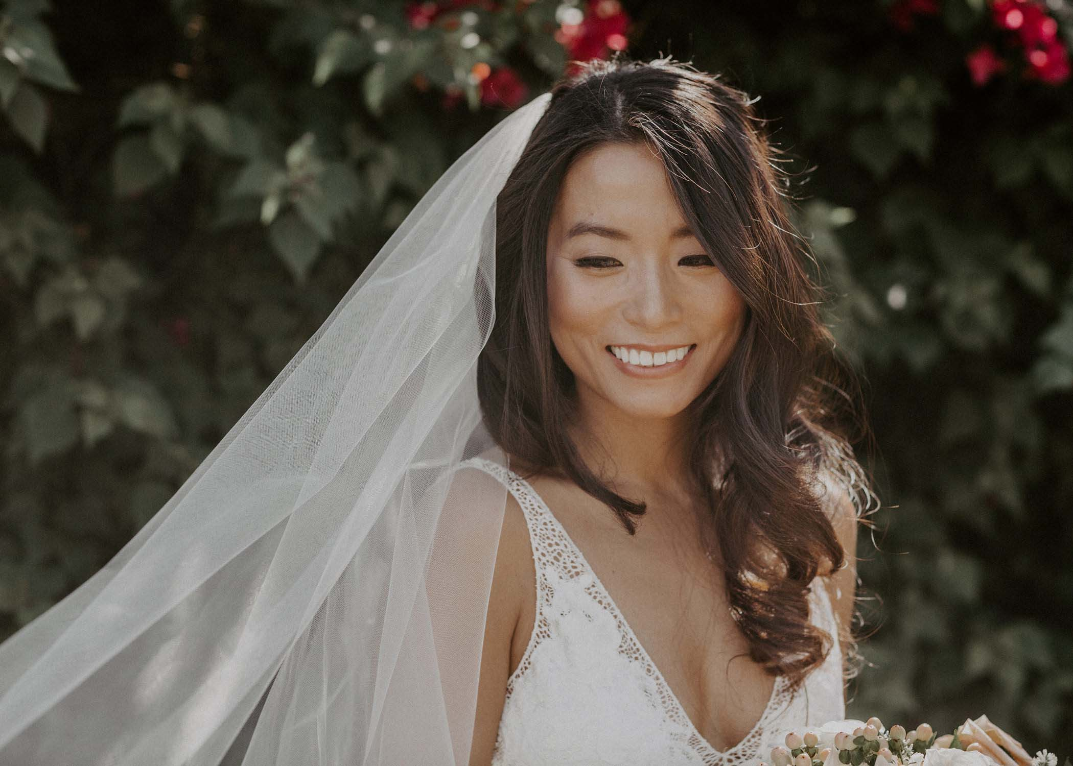 A smiling bride with a veil and bouquet against green wall during an intimate wedding