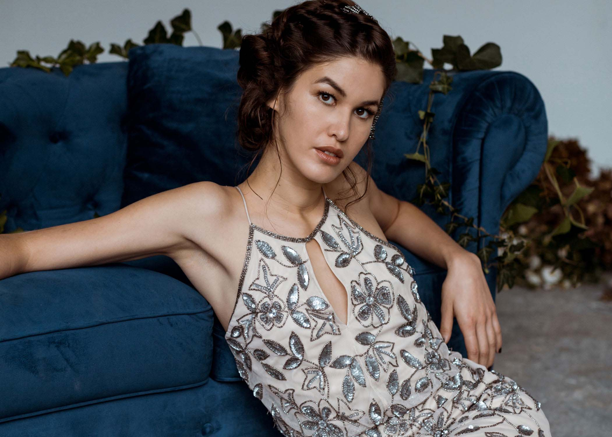 A bride sitting against blue couch from a lookbook, commercial, editorial shoot